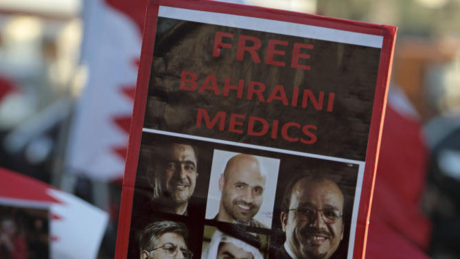 """Senior nurse Rula al Saffar carries a sign with images of jailed Bahraini medics during an anti-government march Sunday, Feb. 3, 2013, in the western village of Malkiya, Bahrain. Hundreds shouted """"down with the government"""" during the march which was called by several opposition groups to demand freedom for political prisoners and democracy in the Gulf island kingdom. (AP Photo/Hasan Jamali)"""