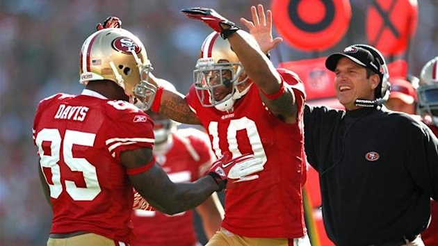 San Francisco 49ers tight end Vernon Davis (L) is congratulated by teammate Kyle Williams (C) and head coach Jim Harbaugh after his first quarter touchdown catch during their NFL NFC Divisional playoff football game in San Francisco