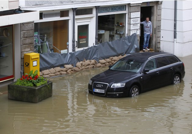 Man looks at flood water from doorway of electrical shop in centre of Passau