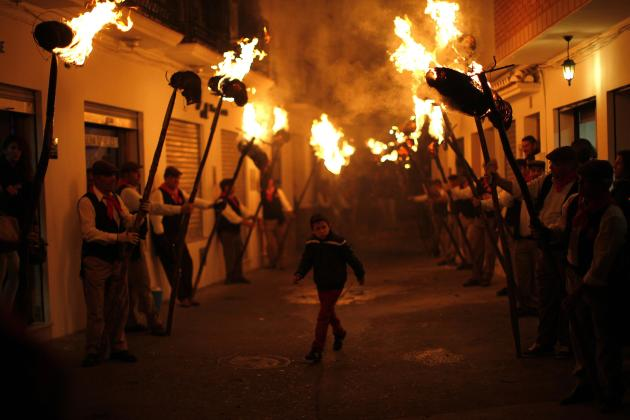 A boy walks between villagers holding torches during the Divina Pastora procession in Casarabonela