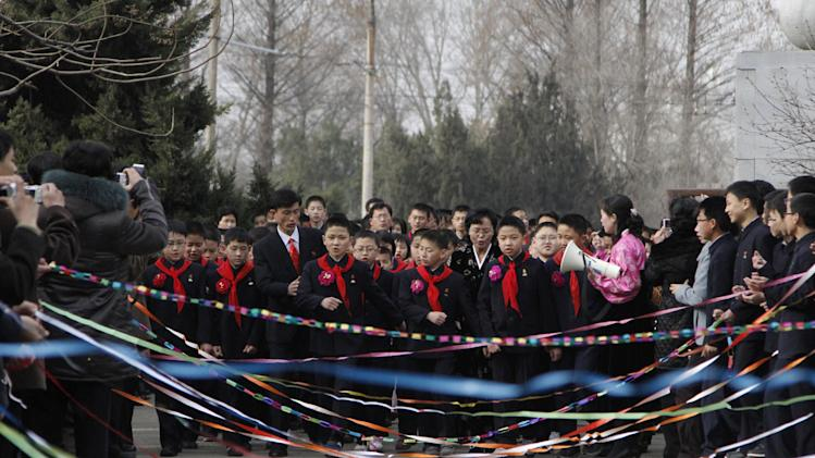 In this Monday, April 2, 2012 photo, North Korean students break through lines of colorful ribbons as they arrive for their first day back to school during a ceremony to mark the start of a new school year at Pyongyang Middle School No. 1 in Pyongyang North Korea. (AP Photo/Jon Chol Jin)