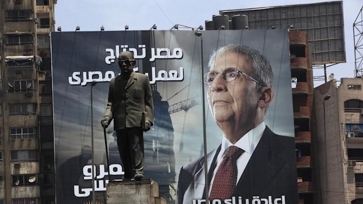 "A statue of Egypt's Nobel laureate Naguib Mahfouz is back dropped with an electoral poster of presidential candidate Amr Moussa and Arabic writing which reads, ""Egypt's reconstruction needs the effort of all Egyptians,"" in Cairo, Egypt, Tuesday, May 8, 2012. The 76-year-old Moussa presents himself as an elder statesman with years of experience in politics and government, first from a decade as foreign minister under former President Hosni Mubarak, then from another decade leading the Arab League. The first round of presidential elections is set for May 23-24. (AP Photo/Nasser Nasser)"