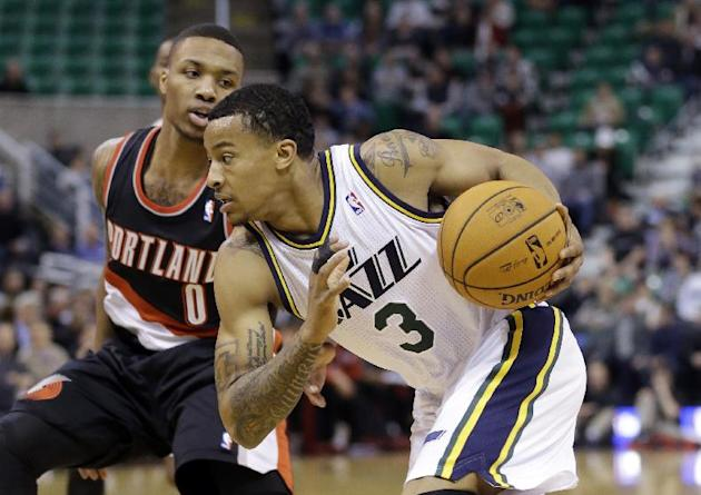 Utah Jazz's Trey Burke (3) drives as Portland Trail Blazers' Damian Lillard (0) stands by in the first quarter during an NBA basketball game Monday, Dec. 9, 2013, in Salt Lake City