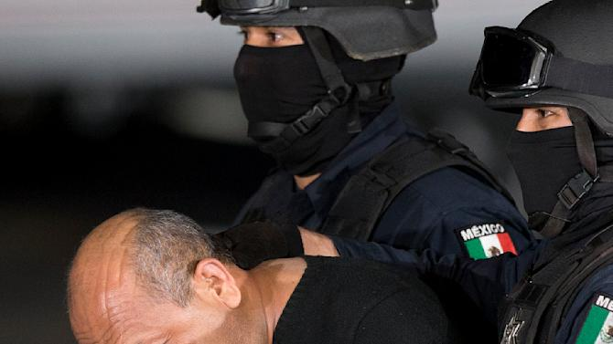 "Federal police escort who they identify as Servando ""La Tuta"" Gomez,"" leader of the Knights Templar cartel, during a news conference at a Federal hanger in Mexico City, Friday, Feb. 27, 2015. Gomez, a former school teacher who became one of Mexico's most-wanted drug lords as head of the Knights Templar cartel, was captured early Friday by federal police, according to Mexican officials. (AP Photo/Eduardo Verdugo)"