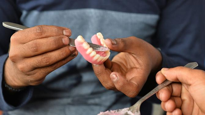 Street dentist Imran Pasha prepares a new set of dentures for a customer at a roadside stall at K.R. Market bus stand in Bangalore