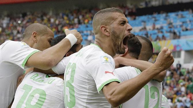 Algeria's Islam Slimani, who scored his side's first goal, celebrates with teammates after Algeria's Rafik Halliche scored the side's second goal during the group H World Cup soccer match between South Korea and Algeria at the Estadio Beira-Rio in Porto Alegre, Brazil, Sunday, June 22, 2014