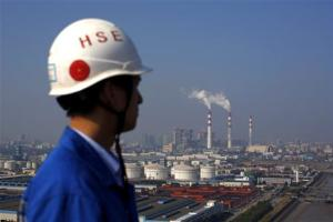 Smoke rises from the chimneys of a thermal power plant as a worker stands on a crane at a shipyard in Shanghai