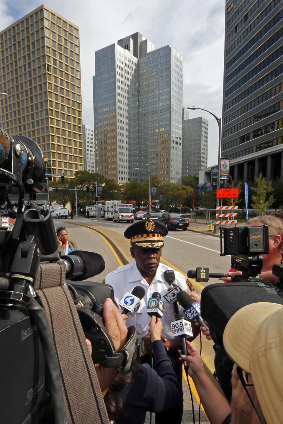 Pittsburgh Police Chief Nate Harper, center, briefs media outside the 3 Gateway Center building, rear center, in downtown Pittsburgh, Friday, Sept. 21, 2012. Police are trying to negotiate with a man claiming to have a bomb and a gun on the 16th floor of the 3 Gateway Center building. (AP Photo/Gene J. Puskar)
