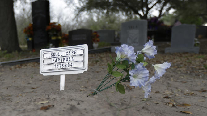 In this Feb. 22, 2013 photo, a sign and plastic flower mark the Falfurrias, Texas grave for the unidentified remains of a suspected illegal immigrant discovered in South Texas. The death of migrants crossing the Southwest border has long been a tragic consequence of illegal immigration and, many say, the massive increase in U.S. border enforcement. For some, the tragedies are a powerful motivator in pushing Congress to act this year on a larger immigration reform package. (AP Photo/Eric Gay)