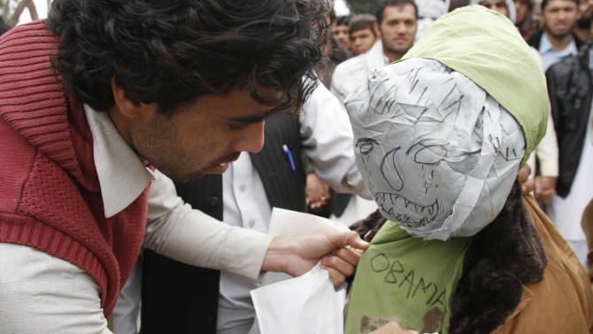 A demonstrator writes on an effigy depicting U.S. President Barack Obama before setting it on fire following Sunday's killing of civilians in Panjwai, Kandahar by a U.S. soldier during a protest in Jalalabad east of Kabul, Afghanistan, Tuesday, March 13, 2012. Hundreds of students in eastern Afghanistan on Tuesday shouted angry slogans against the United States and the American soldier accused of carrying out the killings, the first significant protest in response to the tragedy. (AP Photo/Rahmat Gul)