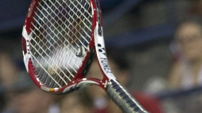 Hewitt of Australia throws his racquet after losing a point to compatriot Tomic during their second round match at the U.S. Open Championships tennis tournament in New York