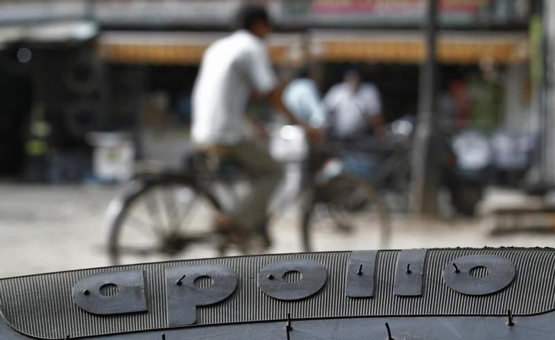 A cyclist rides past an Apollo tyre kept on display at a multi-brand tyre showroom in New Delhi