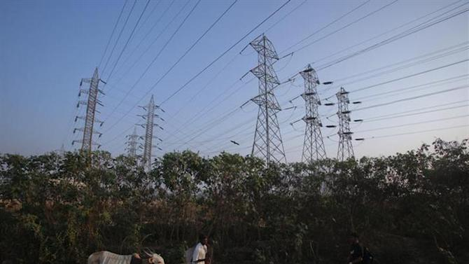 A man walks his cow under high-tension power lines in Mumbai's suburbs February 10, 2013. REUTERS/Vivek Prakash/Files