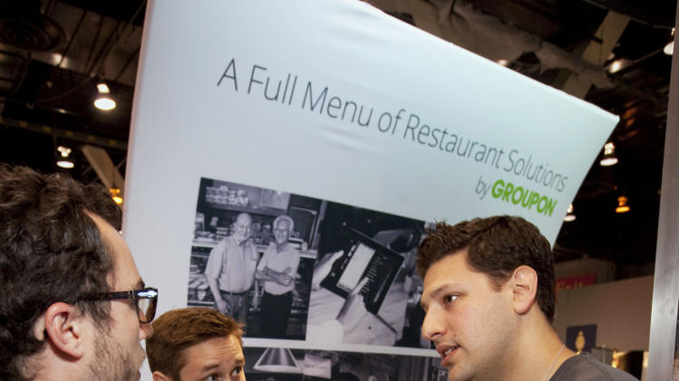 IMAGE DISTRIBUTED FOR GROUPON - Seth Harris, founder of Groupon's Breadcrumb point-of-sale system, talks with exhibitors at the National Restaurant Association Tradeshow at McCormick Place, on Sunday, May 19, 2013 in Chicago. Groupon highlights the company's marketing and Breadcrumb by Groupon point-of-sale and payments at the tradeshow.  (John Konstantaras / AP Images for Groupon)