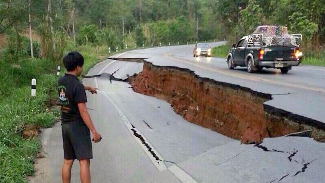 A man points a big crack on a damaged road following a strong earthquake in Phan district of Chiang Rai province, northern Thailand, Monday, May 5, 2014. A strong earthquake shook northern Thailand and Myanmar Monday evening, and some light damage was reported. (AP Photo)