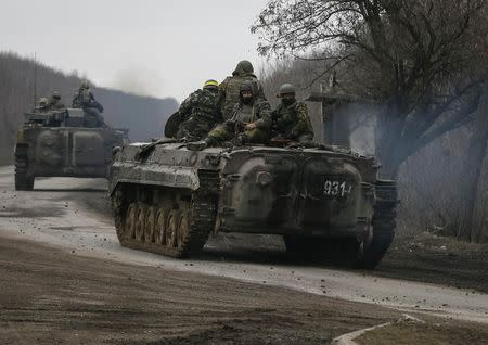 Members of the Ukrainian armed forces ride on armoured personnel carriers near Artemivsk
