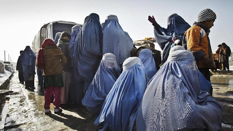 Afghan women wait to receive winter relief assistance donated by the United Nation's refugee agency (UNHCR) outside a refugee camp in Kabul, Afghanistan, Sunday, Dec. 30, 2012. Around 600 internally displaced families received winter relief assistance distributed by the United Nation's refugee agency. (AP Photo/Musadeq Sadeq)