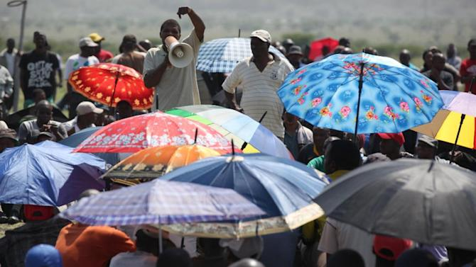 Striking miners at AMPLATS gather to listen to a speaker near Rustenburg, South Africa, on Wednesday, Nov. 14, 2012. Workers discussed a possible deal with Anglo American Platinum, or Amplats, on Wednesday as their weeks-long strike continued. Amplats is the world's top producer of platinum. (AP Photo/Jon Gambrell)