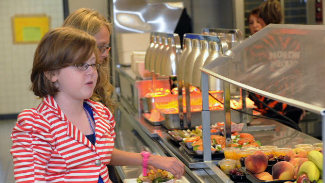 Clara Zonis ,front, and Kelsey Hiscock select food items from the lunch line of the cafeteria at Draper Middle School in Rotterdam, N.Y., Tuesday, Sept. 11, 2012. The leaner, greener school lunches served under new federal standards are getting mixed grades from students. (AP Photo/Hans Pennink)