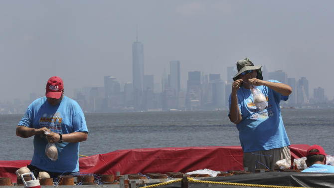 Pyro Spectaculars by Souza workers have a backdrop of a hazy lower Manhattan skyline as they load shells into mortars on a barge docked in the Staten Island borough of New York, Saturday, June 29, 2013. Forty thousand shells are being loaded onto four barges in preparation for the Macy's Fourth of July fireworks display. (AP Photo/Mary Altaffer)