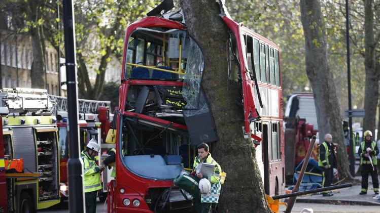 A members of the emergency services walks in front of a bus which crashed into a tree in Kennington, south London