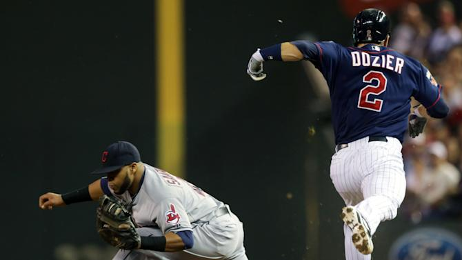 Cleveland Indians first baseman Carlos Santana, left, makes the out as the throw beats Minnesota Twins' Brian Dozier after a grounder in the first inning of a baseball game, Friday, Sept. 19, 2014, in Minneapolis. (AP Photo/Jim Mone)
