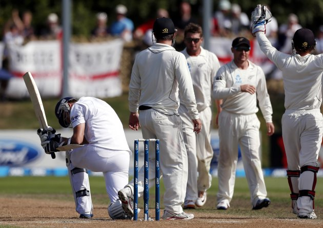 England's Finn reacts after being dismissed for 56 runs as New Zealand players celebrate during the fifth day of the first test at the University Oval in Dunedin