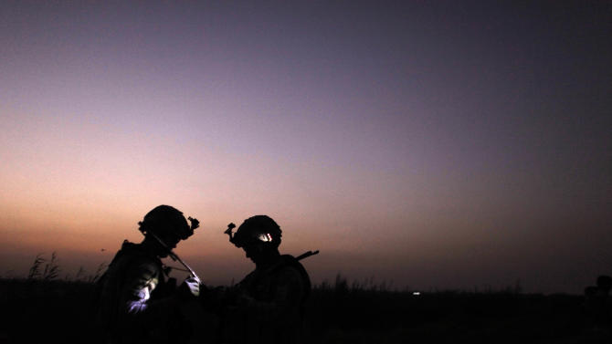 FILE - In this Sunday, Aug. 7, 2011 file photo. U.S. Army soldiers from D Co., 1st Battalion, 18th Infantry Regiment, confer during a patrol outside Contingency Operating Site Taji, north of Baghdad, Iraq. August marks the first month since the 2003 U.S.-led invasion of Iraq that no American forces have died. Figures compiled by The Associated Press show that there were no American forces killed in Iraq in August either in combat or non-combat related situations. (AP Photo/Maya Alleruzzo, File)