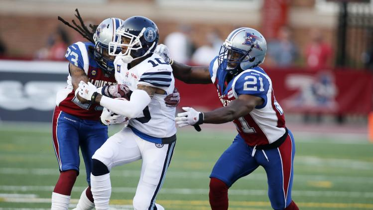 Toronto Argonauts' Robert Gill is tackled by Montreal Alouettes' Mike Edem and Chris Smith during first half CFL football action in Montreal