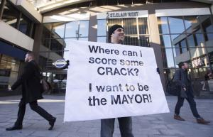 Nic Bibassis holds a sign outside of where Toronto …