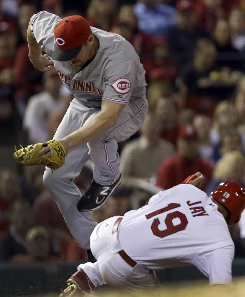 Cincinnati Reds third baseman Scott Rolen, top, tries to avoid the slide of St. Louis Cardinals' Jon Jay after tagging Jay out at third during the third inning of a baseball game, Tuesday, Oct. 2, 2012, in St. Louis. (AP Photo/Jeff Roberson)