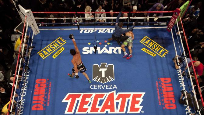 Juan Manuel Marquez, left, begins to celebrate as referee Kenny Bayless calls Manny Pacquiao down for the count in the sixth round during a WBO welterweight fight, Saturday, Dec. 8, 2012, in Las Vegas. (AP Photo/Julie Jacobson)