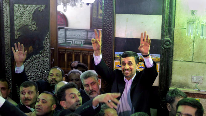 Iran's President Mahmoud Ahmadinejad, center, waves to Egyptian worshippers after he visits the shrine of Imam Hussein, the grandson of Islam's Prophet Mohammad, in Cairo, Egypt, Tuesday, Feb. 5, 2013. Egypt's most prominent Muslim cleric, the sheik of Al-Azhar, has warned Iranian President Mahmoud Ahmadinejad against interfering in Arab Gulf countries or trying to spread Shiite influence. Ahmadinejad, on a landmark visit to Egypt on Tuesday, received an uneasy reception from Ahmed el-Tayeb at Al-Azhar, the Sunni Muslim world's foremost Islamic institution.(AP Photo/Amr Nabil)