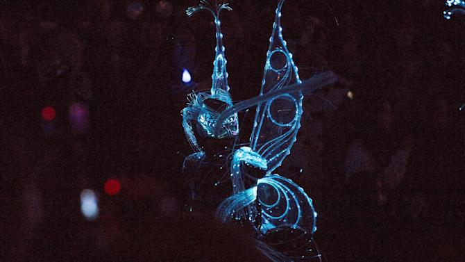 """A performer dances during the """"Paint the Night - All-New Electrical Parade"""" during Disneyland's Diamond Celebration in Anaheim"""