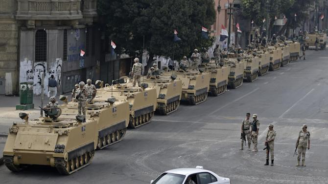 """Egyptian army soldiers take their positions on top and next to their armored vehicles while guarding an entrance to Tahrir square, in Cairo, Egypt, Friday, Aug. 16, 2013. Egypt is bracing for more violence after the Muslim Brotherhood called for nationwide marches after Friday prayers and a """"day of rage"""" to denounce this week's unprecedented bloodshed in the security forces' assault on the supporters of the country's ousted Islamist president that left more than 600 dead. (AP Photo/Hassan Ammar)"""