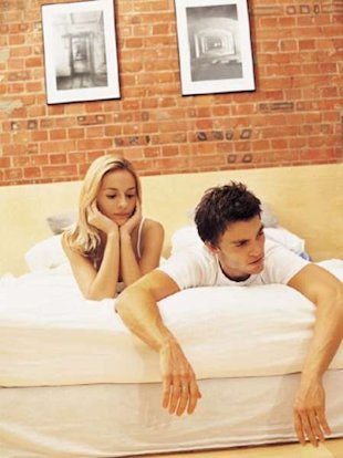 Unhappy couple lying on bed