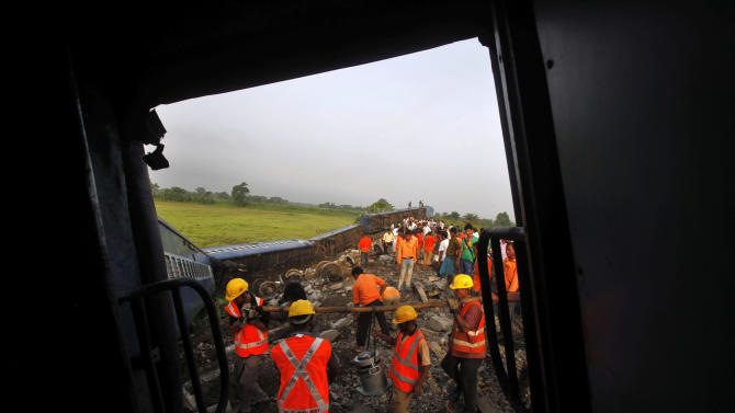 Indian Railway workers remove debris of a derailed passenger train near Bhatkuchi, about 70 km (43 miles) west of Gauhati, India, Monday, July 11, 2011. Police said Adivasi Peoples' Army militant group was suspected of triggering a bomb that led to the derailment of the train Sunday. (AP Photo/Anupam Nath)