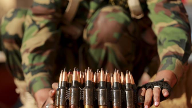 A personnel of pro-government Libyan forces, who are backed by locals, arranges ammunition during clashes in Benghazi