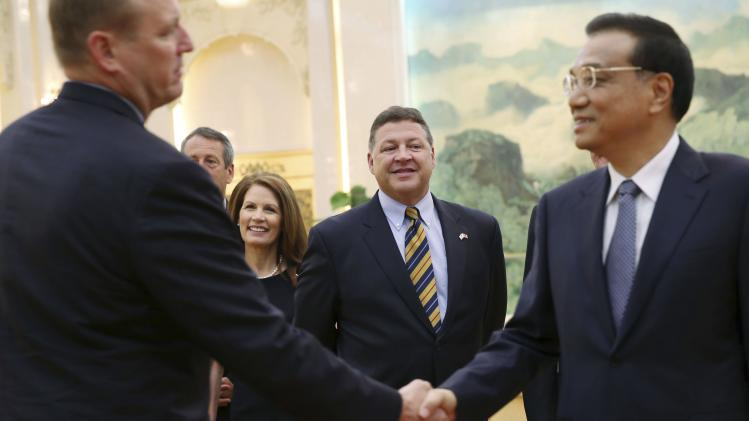 U.S. Chair of the House Committee on Transportation and Infrastructure Shuster and U.S. Representative Bachmann looks on as Chinese Premier Li shakes hands with a U.S. delegate in Beijing