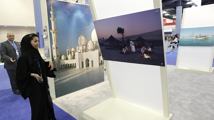 Noura Al Dhaheri, of the Abu Dhabi Tourism and CultureAuthority, works at an exhibit promoting tourism in the United Arab Emirates during a trade show for the cruise ship industry at the annual Cruise Shipping Miami conference, Tuesday, March 11, 2014, in Miami Beach, Fla. (AP Photo/Lynne Sladky)