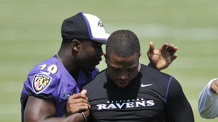 Baltimore Ravens running back Ray Rice, right, walks off the field with Justin Forsett before addressing the media at a news conference after NFL football training camp practice, Thursday, July 31, 2014, in Owings Mills, Md.(AP Photo/Gail Burton)