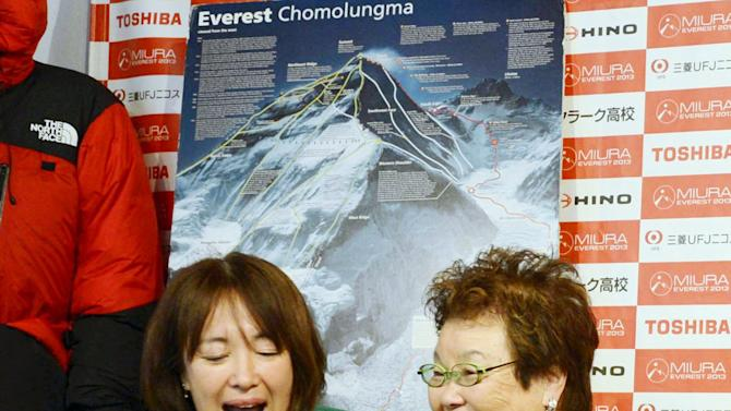 ADDS LOCATION - From left: Emiri Miura, daughter, and Tomoko Miura, wife of 80-year-old Japanese mountaineer Yuichiro Miura speaks with him immediately after he conquered the summit of Mount Everest, at Miura's office in Tokyo on Thursday, May 23, 2013. Miura on Thursday became the oldest person to reach the top of Mount Everest, although his record may last only a few days. An 81-year-old Nepalese man, who held the previous record, plans his own ascent next week. (AP Photo/Kyodo News) JAPAN OUT, MANDATORY CREDIT