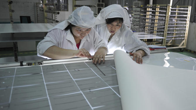 In this July 17, 2013 photo, workers assemble solar panels at a factory in Hefei, in central China's Anhui province. The Europe Union and Chinese solar panel exporters said Saturday, July 27, 2013 that they had reached a settlement in their long trade dispute, with the exporters agreeing to sell their products at a minimum price in the EU market. (AP Photo) CHINA OUT