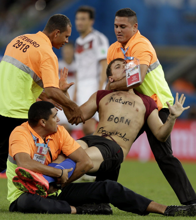 A spectator who ran on to the pitch during the World Cup final soccer match between Germany and Argentina is subdued by security personnel at the Mara...