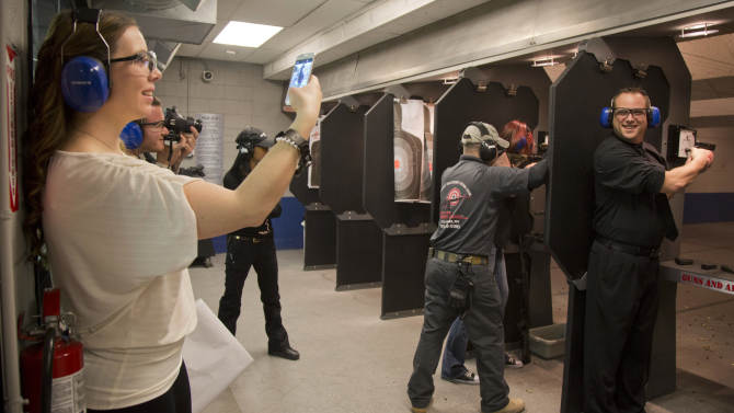 Tanya Morris, left, takes a photo of her new husband, Ted Morris on the shooting range after getting married at the Guns and Ammo Garage, Thursday, Feb. 14, 2013, in Las Vegas. Never known for its understatement or good taste, Sin City is bucking the national trend of avoiding flippant gun promotions after the Newton, Conn., elementary school shooting. Instead, it is embracing tourists' newfound interest in big guns the only way it knows how: by going all in.  (AP Photo/Julie Jacobson)
