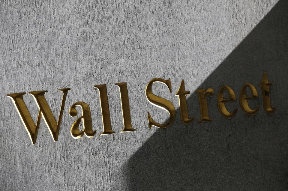 A sign for Wall Street is displayed on the side of building near the New York Stock Exchange, Monday, March 4, 2013. Uncertainty over the outcome of a budget battle in Washington pushed world stock markets lower on Monday. (AP Photo/Mark Lennihan)