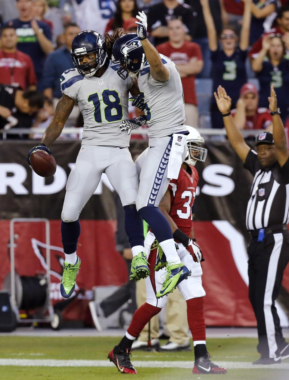 Seattle Seahawks wide receiver Sidney Rice (18) celebrates his touchdown with Jermaine Kearse, right, as Arizona Cardinals strong safety Yeremiah Bell, rear, walks away during the first half of an NFL football game, Thursday, Oct. 17, 2013, in Glendale, Ariz. (AP Photo/Ross D. Franklin)