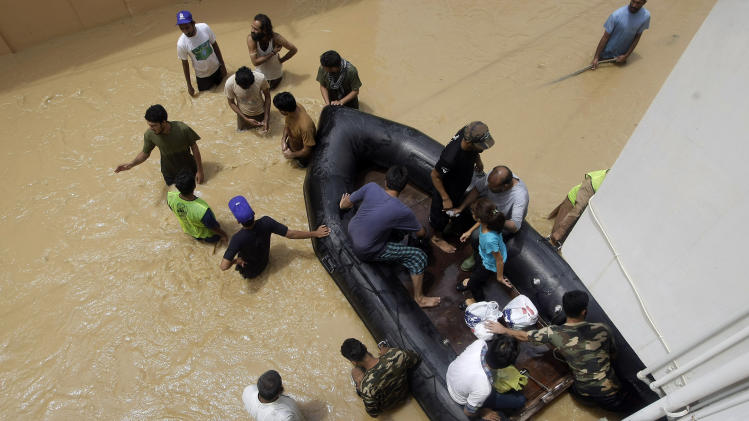 Pakistani soldiers rescue local residents from an area flooded by heavy rains on the outskirts of Karachi, Pakistan, Sunday, Aug. 4, 2013. Heavy rains that swept across Pakistan brought down more than 100 homes and caved in a factory wall, killing at least a dozen people in the downpours, officials said. (AP Photo/Fareed Khan)