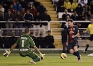 Barcelona's Lionel Messi (R) scores his second goal past Rayo Vallecano's goalkeeper Ruben Martinez during their Spanish La Liga match at the Vallecas stadium in Madrid. Messi smashed through the 300-goal mark with a brace as Barcelona won 5-0