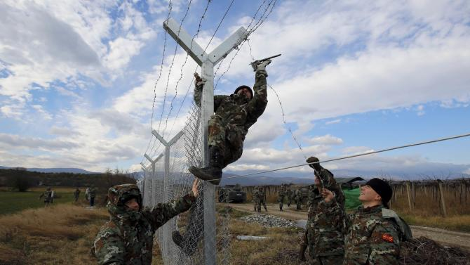 Macedonian soldiers erect a barbed wire fence on the Macedonian-Greek border, near Gevgelija